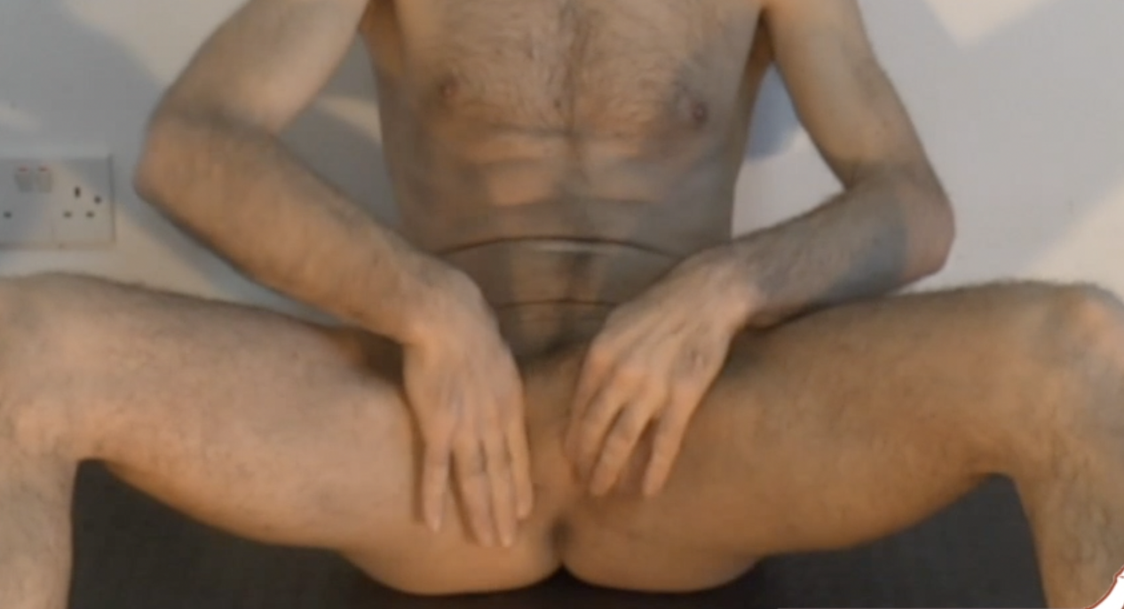 Naked man sitting with legs up and wide whilst holding testicles and penis out of the way so you can see the male pelvic floor muscles